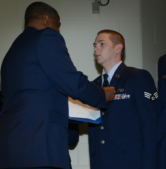 Brig. Gen. Brian Newby, chief of staff for the Texas Air National Guard pins the Texas Medal of Merit on Senior Airman Joushua Long, 136th Airlift Wing Airman of the Year for his outstanding performance in the Wing. Long competed amongst fellow Airmen thoughout the State. (National Guard photo by Senior Master Sgt. Elizabeth Gilbert)