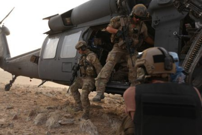 """David Clawson, a member of the National Geographic film crew, captures the action for """"Inside Combat Rescue"""" as pararescuemen from Moody Air Force Base, Ga., exit their helicopter after touching down in in a remote area of Afghanistan. The show is a Department of Defense supported Nat Geo television series about Air Force combat rescue efforts in Afghanistan. (National Geographic Channel photo by Jared McGilliard)"""