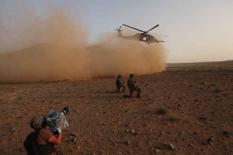 """David Clawson, a member of the National Geographic film crew, captures the action as pararescuemen from Moody Air Force Base, Ga., secure the area while an HH-60 Pave Hawk lifts off.  A five-person Nat Geo television crew filmed """"Inside Combat Rescue"""" for five weeks with Airmen from Moody AFB and Pave Hawk crews from Nellis AFB, Nev., at Kandahar Airbase, Afghanistan. (National Geographic Channel photo by John Collin)"""