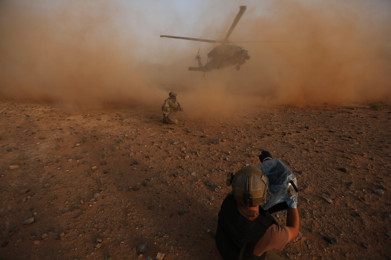 """David Clawson, a member of the National Geographic film crew, captures the action as a pararescueman from Moody Air Force Base, Ga., secure the area while an HH-60 Pave Hawk arrives to whisk them out of harm's way.  In a first-of-its-kind project, Nat Geo had unprecedented access to all aspects of the Air Force rescue mission in Afghanistan for a new television series called """"Inside Combat Rescue."""" (National Geographic Channel photo by John Collin)"""
