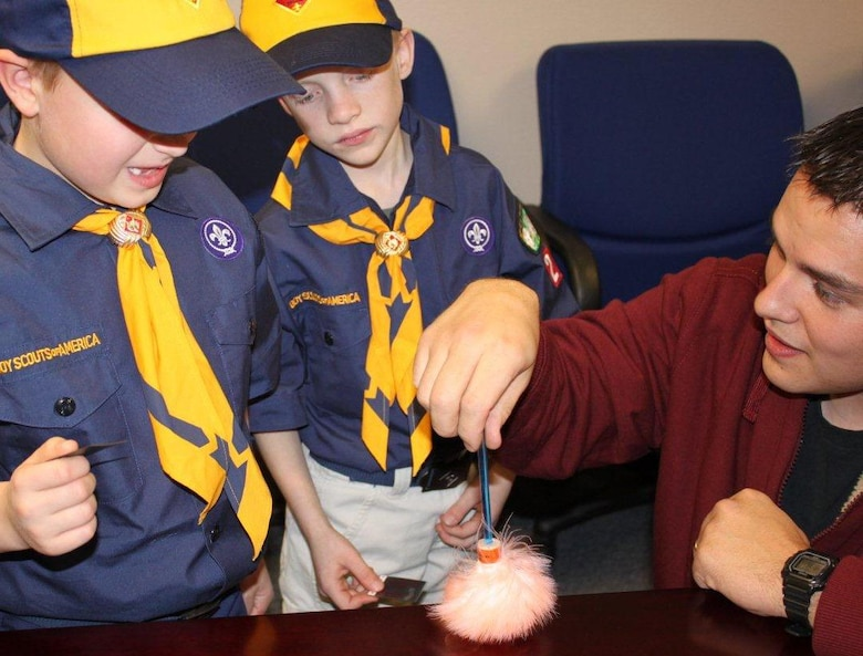 "Special Agent Benjamin Tallman, OSI Detachment 226, Ellsworth Air Force Base, S.D., shows two cub scouts from a local cub scout den how to brush for fingerprints. The scouts were invited to the detachment to fulfill a requirement toward getting their ""wolf badge."" (U.S. Air Force Photo/OSI Det. 226)"