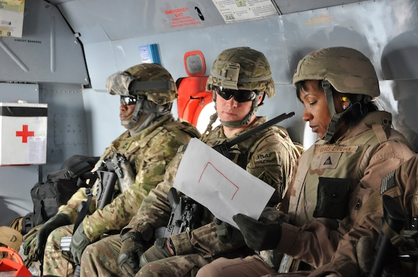 Lori Gardner (right), the Afghanistan Engineer District-South Tarin Kowt Resident Office Engineer, and Capt. Daniel Sunden, the resident office officer in charge, review site plans on a helicopter ride to a U.S. Army Corps of Engineers project site in Uruzgan province, Afghanistan.