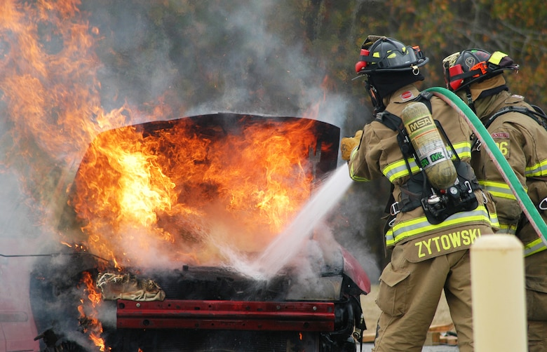 Robins firefighters Daniel Zytowski and John Whitson extinguish a car fire during a training exercise Jan. 10. The exercise scenario involved a two-car accident involving one vehicle on fire with an injured person outside of the car and two injured passengers in the second car on Beale Drive near Bldg. 10.(U. S. Air Force photo/Sue Sapp)