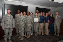 Col. Jeffrey Flewelling (left), 21st Space Wing vice commander, and Chief Master Sgt. Richard Redman (right), 21st SW command chief, present the Gold Knight award to a joint team who provided exercise support to a button-up exercise at Cheyenne Mountain Air Force Station. (U.S. Air Force photo)