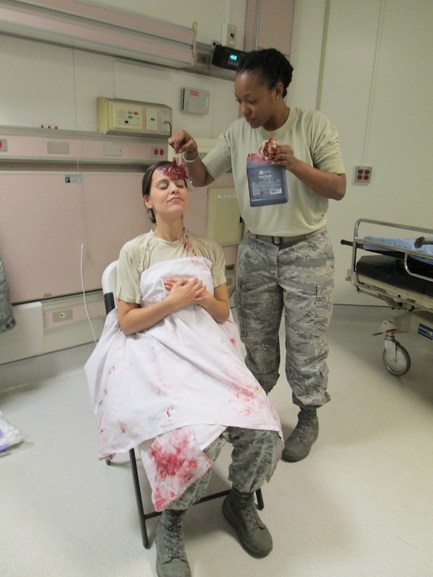 Tech Sgt. Erin Connolly (right) paints a moulage on Staff Sgt. Jennifer Cummings intended to simulated head trauma for a medical training held at Joint Base Andrews, January 10, 2013. The training is to prepare a medical team for their role in the 57th Presidential Inauguration as a medical response unit. Connolly is medical engineer and Cummings is a lab technician, both with the 79th Medical Wing. (U.S. Air Force Photo/Melanie Moore)