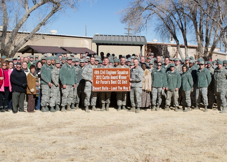 Col. Andrew Croft, 49th Wing commander and Command Chief Master Sergeant James Patrie, pose for a photo with the 49th Civil Engineer Squadron after being recognized as the best large civil engineer squadron in the Air Force at Holloman Air Force Base, N.M., Jan. 16. The 49th CES won the highly-coveted Curtin Award, created by the Society of American Military Engineers in 1966, which recognizes the most outstanding large, small and Reserve civil engineer units in the Air Force every year. (U.S. Air Force photo by Senior Airman DeAndre Curtiss/Released)