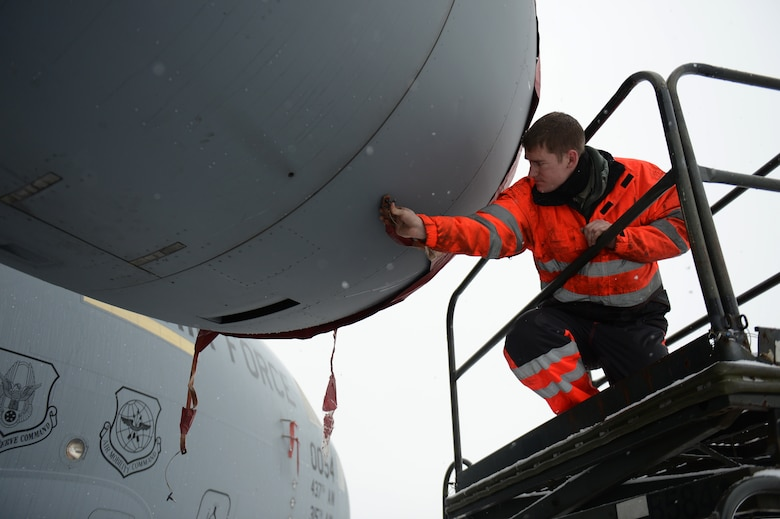 SPANGDAHLEM AIR BASE, Germany – U.S. Air Force Senior Airman Daryl Treadwell, 726th Air Mobility Squadron integrated flight control systems technician from Austin, Texas, applies an engine cover to a C-17 Globemaster III cargo aircraft Jan. 15, 2013.  The four engines are covered to prevent snow from accumulating in the engine inlets. (U.S. Air Force photo by Airman 1st Class Gustavo Castillo/Released)