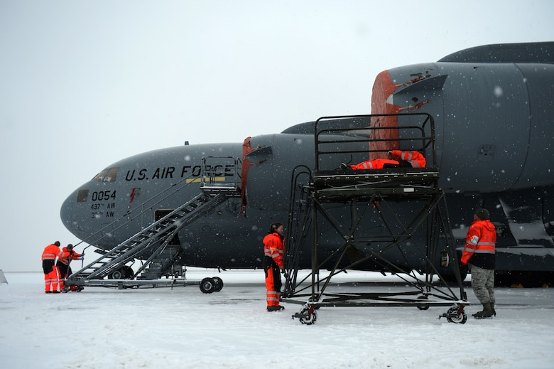 SPANGDAHLEM AIR BASE, Germany – Airmen from the 726th Air Mobility Squadron secure engine covers on a C-17 Globemaster III cargo aircraft Jan. 15, 2013. The covers are secured by six pins and then tightened to reduce the effects of extreme weather conditions on an engine at rest. (U.S. Air Force photo by Airman 1st Class Gustavo Castillo/Released)