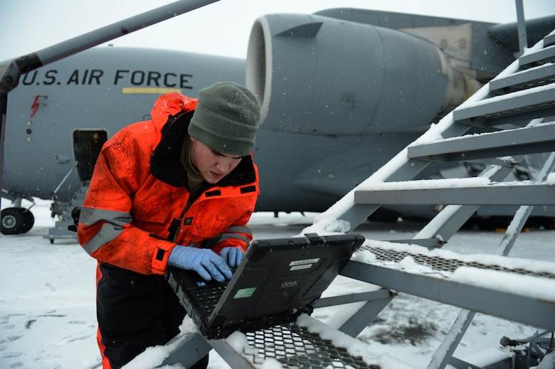 SPANGDAHLEM AIR BASE, Germany – U.S. Air Force Senior Airman Craig Fox, 726th Air Mobility Squadron hydraulics technician from Glen Burnie, Md., reads a technical order on his laptop prior to working on a C-17 Globemaster III cargo aircraft Jan. 15, 2013. Maintainers from the 726th prepared the aircraft for a winter storm that hit the base recently. (U.S. Air Force photo by Airman 1st Class Gustavo Castillo/Released)