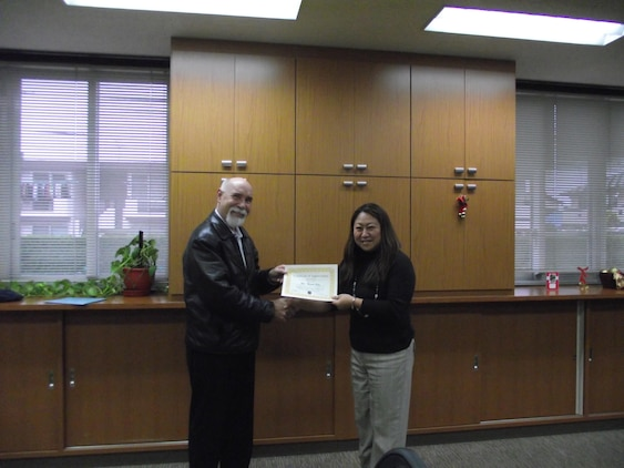 Gary Bernhard, Marine All-Weather Fighter Attack Squadron 242 family readiness officer, presents Miyuki Gray, Japanese Lifestyle Insights, Networking, Knowledge, and Skills trainer, a certificate of appreciation for her volunteer work at the Marine Corps Family Team Building, Dec. 17, 2012. Gray received the award helping supply an American spouse with a Japanese translator to find a daycare in town. Gray volunteers her time away from work to ensure that Japanese spouses are comfortable adapting to a military lifestyle as well as an American one.