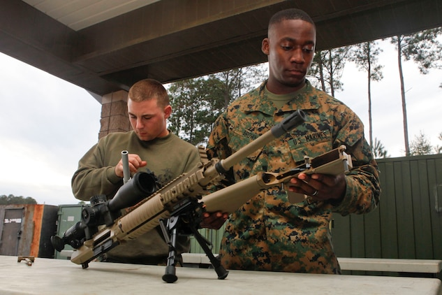 Lance Cpl. Emmanuel Brown, left, and Cpl. Emmanuel Brown, right, Marine Fighter Attack Squadron 273 small-arms repair technicians, inspect a M110 rifle while aboard the Air Station, Jan. 7. Marines who live in the barracks aboard the Air Station are required to use the station's armory for storing their firearms, however, any Marine may use the armory to store personal firearms.