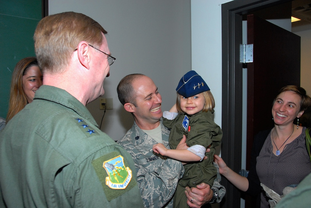 Lt. Col. Travis Zimmer of the 908th Airlift Wing, along with wife, Amy, react as Lt. Gen. David Fadok, commander and president of Air University shares his three-star cover with the Zimmer's daughter, Florence, prior to the deployment of Airmen from the 908th Jan. 10. (U.S. Air Force photo by Gene H. Hughes)