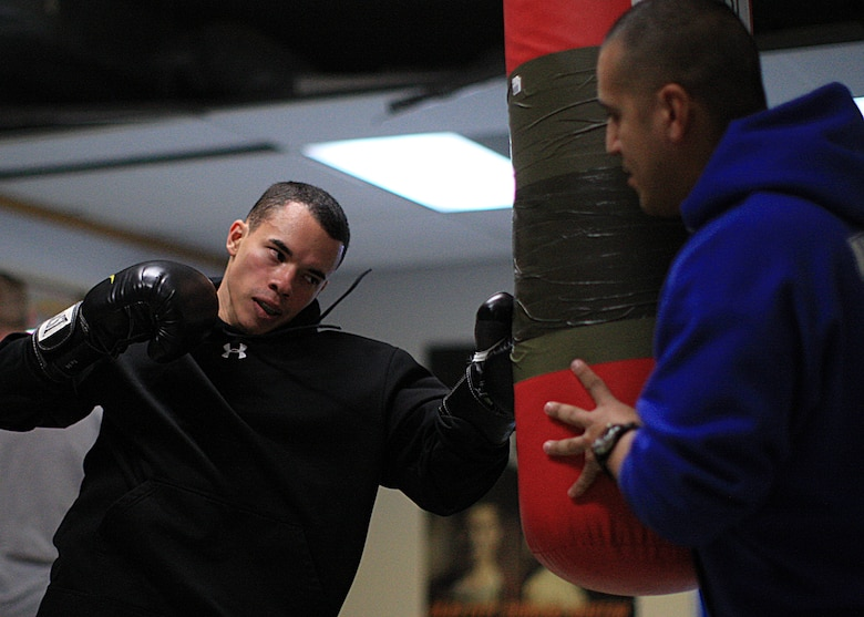 Senior Airman Richard Purrier, 90th Security Forces Group Tactical Response Force, swings at a heavy bag held by his coach, Tech. Sgt. Bobby De Leon, 90th SFG TRF team lead, during training Jan. 10 on F. E. Warren Air Force Base, Wyo. Purrier trains daily to prepare for his upcoming competition for selection to the All Air Force Boxing Team Jan. 21 at Lackland Air Force Base, Texas. (U.S. Air Force photo by Matt Bilden)