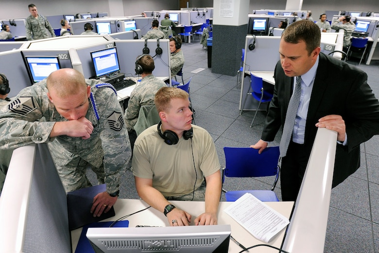 Master Sgt. Jesse Chervinka and Jessie Rhom help a cadet process an Electronic Questionnaire for Investigations Processing, or e-QIP, form in the Foreign Language Lab here Jan. 12, 2013. Information Protection Directorate officials process between 650 and 700 cadet applications for top-secret clearance annually. Chervinka is the Academy military training NCO for Cadet Squadron 31. Rhom is the IP Directorate's personnel security chief. (U.S. Air Force photo/Mike Kaplan)