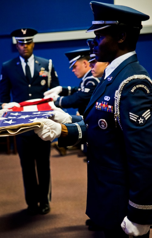 An American flag is folded by the Eglin Honor Guard to be presented to Senior Airman Josh Santos' mother, Lisa, during his memorial Jan. 13 at Duke Field, Fla.  Santos passed away Nov. 26 from colon cancer.  He was a radio operator with the 711th Special Operations Squadron.  During the memorial, it was announced the Duke Field gym would be renamed Santos Strength in his honor.  (U.S. Air Force photo/Tech. Sgt. Samuel King Jr.)