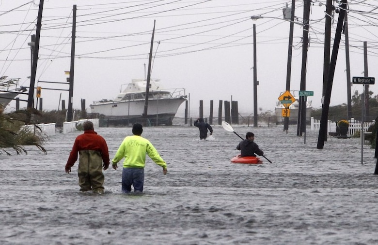 People wade and paddle down a flooded street as Hurricane Sandy approaches, Oct. 29, in Lindenhurst, N.Y. Gaining speed and power through the day, the storm knocked out electricity to more than 1 million people and figured to upend life for tens of millions more.