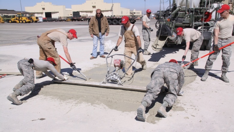 After the U.S. Army Engineer Research and Development Center Airfield Damage Repair (ADR) team train the airmen, members of the Rapid Engineer Deployable, Heavy Operational Repair Squadron Engineer (RED HORSE) squadron practice screeding skills using the materials, equipment and methods to repair craters in preparation for a cold weather demonstration at Malmstrom Air Force Base, Mont