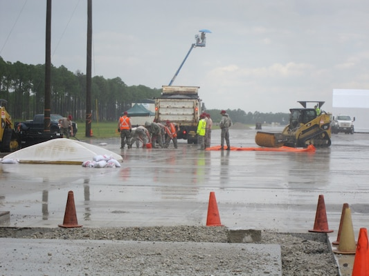 After the U.S. Army Engineer Research and Development Center Airfield Damage Repair (ADR) team train the airmen, members of the Rapid Engineer Deployable, Heavy Operational Repair Squadron Engineer (RED HORSE) squadron use the materials, equipment and methods to repair craters during a simulated wet weather demonstration at Tyndall Air Force Base, Fla. The protective covers are placed the work underway to prevent dilution of the repair materials and over the repaired area to enable rapid set to take place.