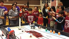 Robo-Ninja team members, coaches, and families look on as their robot performs during the winning table run.