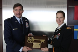 Lt. Col. Michelle Garcia, U.S. Army Corps of Engineers Europe District deputy commander, presents a commemorative key plaque to Lt. Gen. Frank Kisner, NATO Special Operations Headquarters commander, following the unit's headquarters facility ribbon-cutting at SHAPE in Mons, Belgium Dec. 12, 2012. NATO special operations forces, comprised of 26 member nations and 3 non-NATO partners, completed a new, state-of-the-art 23,000-square-foot administrative headquarters building. The USACE-managed $19 million project was completed in 23 months through a partnership with the joint venture contractors Bilfinger-Berger and Besix. During construction, 116 local subcontractors and suppliers were involved and local building materials were utilized. The facility meets strict environmental and energy savings standards and is U.S. Green Buildings Council LEED Silver certifiable.