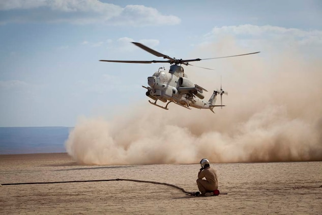 """Lance Cpl. Daniel Aguayo, Mobile Marine Air Traffic Control Team, Marine Medium Helicopter 364 (Rein.), 15th Marine Expeditionary Unit,  runs off a Ch-46E Sea Knight helicopter to begin establishing a runway for a Marine KC-130 during a training evolution in Djibouti, Jan 4.   The mission for the MMT, or """"pathfinders"""" as they're colloquially referred to, is to establish an assault landing zone (runway) and provide air traffic control for multiple aircraft as well as command and control during the entire refuel/resupply mission.  The 15th MEU is deployed as part of the Peleliu Amphibious Ready Group as a U.S. Central Command theater reserve force, providing support for maritime security operations and theater security cooperation efforts in the U.S. 5th Fleet area of responsibility.  (U.S. Marine Corps photo by Gunnery Sgt. Jennifer Antoine)"""