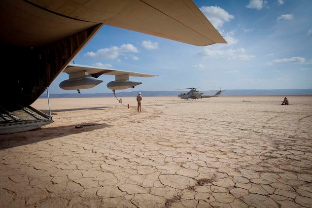 """An AH-1Z Super Cobra with Marine Medium Helicopter 364 (Rein.), 15th Marine Expeditionary Unit, lands to refuel during a Mobile Marine Air Traffic Control training evolution in Djibouti, Jan 4.   The mission for the MMT, or """"pathfinders"""" as they're colloquially referred to, is to establish an assault landing zone (runway) and provide air traffic control for multiple aircraft as well as command and control during the entire refuel/resupply mission.  The 15th MEU is deployed as part of the Peleliu Amphibious Ready Group as a U.S. Central Command theater reserve force, providing support for maritime security operations and theater security cooperation efforts in the U.S. 5th Fleet area of responsibility.  (U.S. Marine Corps photo by Gunnery Sgt. Jennifer Antoine)"""
