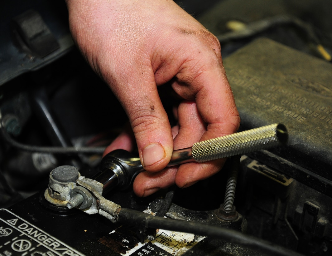 Airman 1st Class Thomas Steinke, 66th Training Squadron survival, evasion, resistance and escape student, tightens the screws on his car battery at the auto hobby shop at Fairchild Air Force Base, Wash., Jan. 18, 2013. Steinke chose to use the auto hobby shop because of the affordable price to rent the bay as well as the convenience of being on base. (U.S. Air Force photo by Airman 1st Class Janelle Patiño)