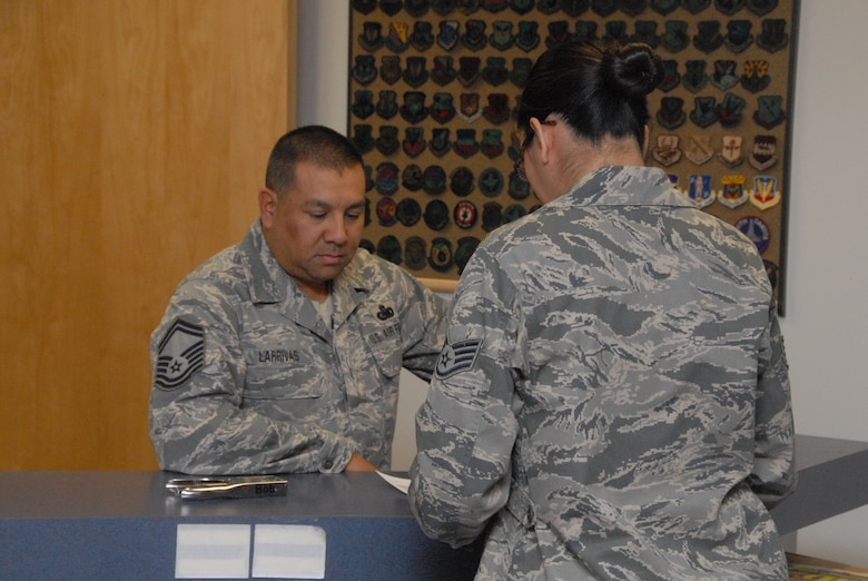 Senior Master Sgt. Daniel Larrivas is fuels supervisor in the Fuel Management Flight discusses uniform options with Staff Sgt. Mia Torres-Gomez, supply technician in the