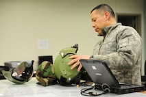 WHITEMAN AIR FORCE BASE, Mo. -- U.S. Army Chief Warrant Officer 4 Jim Nix, 1 -135th Attack Reconnaissance Battalion standardization instructor pilot, re-sizes his helmet for night vision goggle operations, Jan. 16. Pilots perform nighttime operations to prepare for future deployments and to meet training requirements. (U.S. Air Force photo/Staff Sgt. Nick Wilson) (Released)