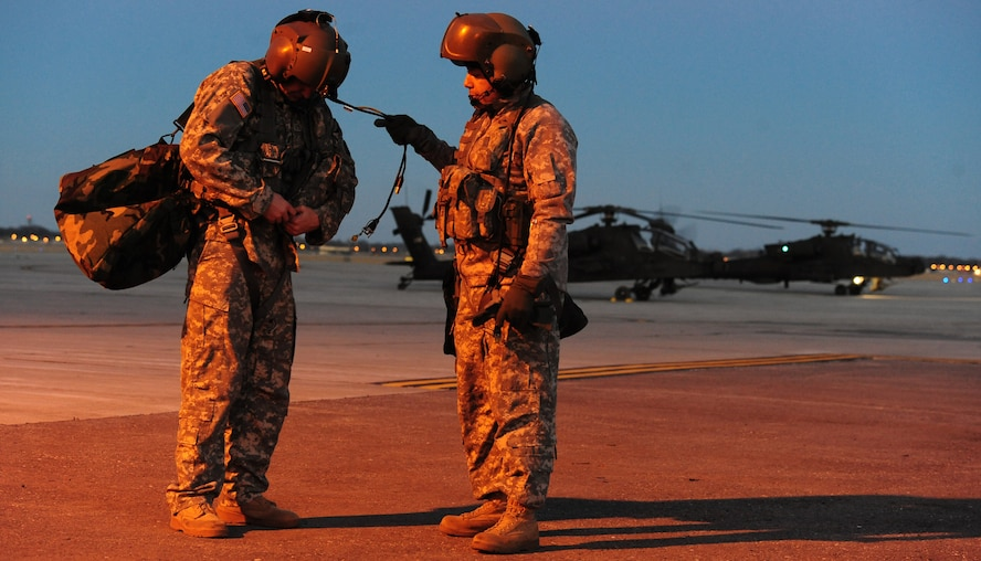 WHITEMAN AIR FORCE BASE, Mo. -- U.S. Army 1st Lt. Khaled Alossi, 1 -135th Attack Reconnaissance Battalion platoon leader, fixes his equipment with the assistance of Chief Warrant Officer 4 Jim Nix, 1 -135th ARB standardization instructor pilot after completing a training mission, Jan. 16. Apache pilots perform two to three missions per pilot each day to prepare for combat. (U.S. Air Force photo/Staff Sgt. Nick Wilson) (Released)