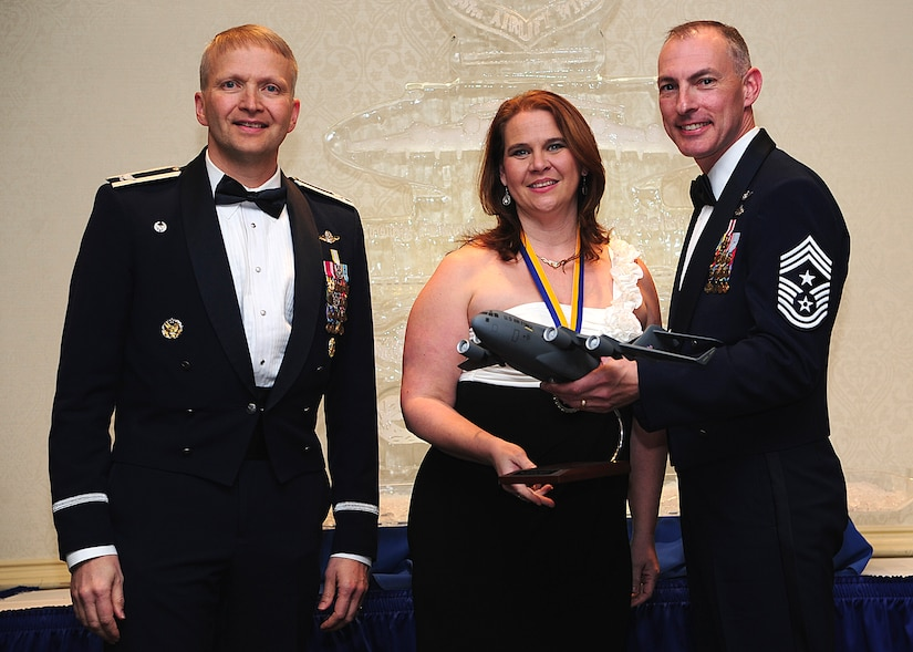Colonel Darren Hartford, 437th Airlift Wing commander, and Chief Master Sgt. Larry Williams, 437th Airlift Wing command chief, present the 437th AW Key Spouse of the Year award to Victoria Thaman during the 437th AW Annual Awards Banquet held at the Charleston Club, Jan. 18, 2013, at Joint Base Charleston - Air Base, S.C. (U.S. Air Force photo/Staff Sgt. Rasheen Douglas)Squadron Operations Group. (U.S. Air Force photo by Staff Sgt. Rasheen Douglas)