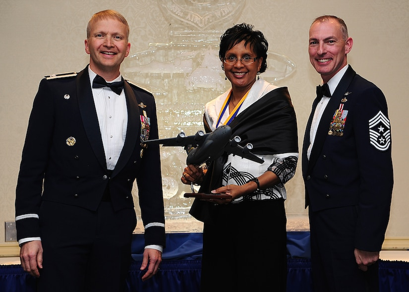 Colonel Darren Hartford, 437th Airlift Wing commander, and Chief Master Sgt. Larry Williams, 437th AW command chief, present the 437th AW Airlift Wing Civilian of the Year, Category One award to Faye Ellison from the 15th Airlift Squadron during the 437th AW Annual Awards Banquet held at the Charleston Club, Jan. 18, 2013, at Joint Base Charleston - Air Base, S.C. (U.S. Air Force photo/Staff Sgt. Rasheen Douglas)