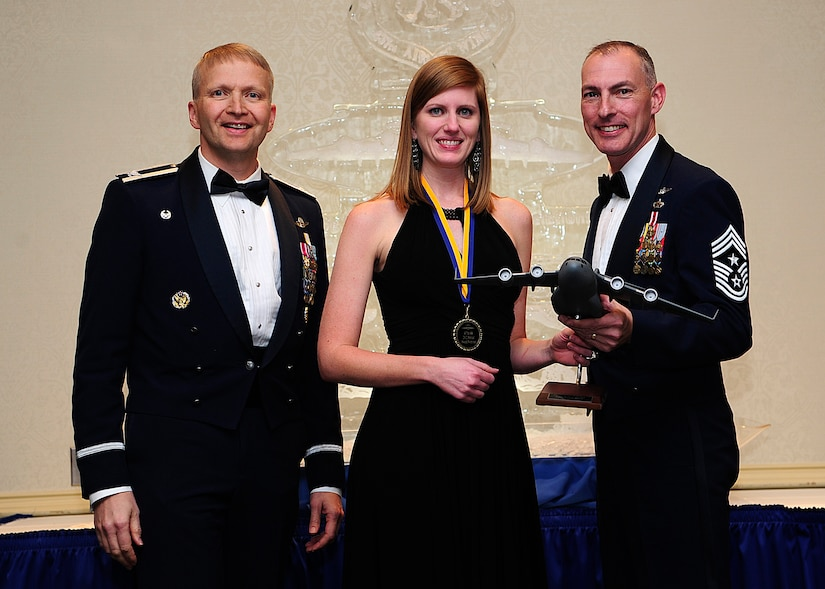 Colonel Darren Hartford, 437th Airlift Wing commander, and Chief Master Sgt. Larry Williams, 437th AW command chief, present the 437th AW Senior Grade Officer of the Year award to Rachel Boyd on behalf of her husband Capt. Adam Boyd from the 15th Airlift Squadron during the 437th AW Annual Awards Banquet held at the Charleston Club, Jan. 18, 2013, at Joint Base Charleston - Air Base, S.C. (U.S. Air Force photo/Staff Sgt. Rasheen Douglas)