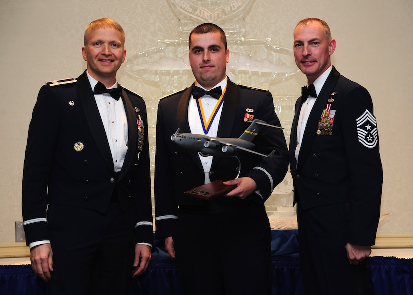 Colonel Darren Hartford, 437th Airlift Wing commander, and Chief Master Sgt. Larry Williams, 437th AW command chief, present the 437th AW Junior Grade Officer of the Year award to 2nd Lt. Jordan Passmore from the 437th APS at the 437th AW Annual Awards Banquet held at the Charleston Club, Jan. 18, 2013, at Joint Base Charleston - Air Base, S.C. (U.S. Air Force photo/Staff Sgt. Rasheen Douglas)