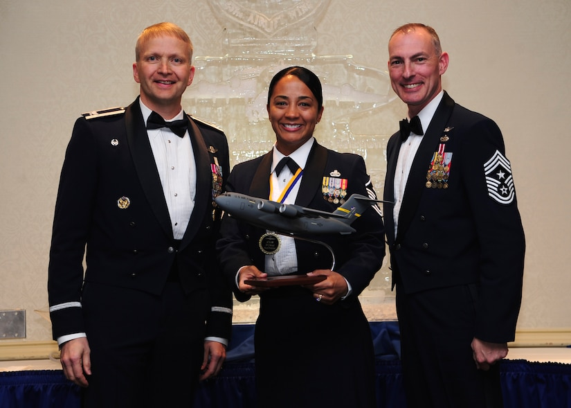 Colonel Darren Hartford, 437th Airlift Wing commander, and Chief Master Sgt. Larry Williams, 437th AW command chief, present the 437th AW First Sergeant of the Year award to Master Sgt. Jadirra Walls from the 437th Maintenance Squadron during the 437th AW Annual Awards Banquet held at the Charleston Club, Jan. 18, 2013, at Joint Base Charleston - Air Base, S.C. (U.S. Air Force photo/Staff Sgt. Rasheen Douglas)
