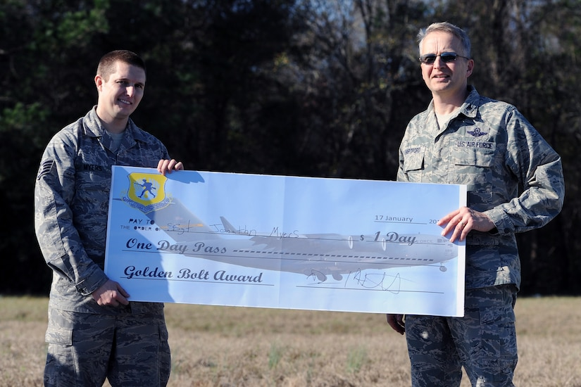 """Col. Darren Hartford, 437th Airlift Wing commander, presents the """"Golden Bolt Award"""" to Staff Sgt. Jonathan Myers, 437th Aircraft Maintenance Squadron, after the Foreign Object Debris walk Jan. 17, 2013, at Joint Base Charleston - Air Base, S.C. By removing FOD from runways and flightlines, Airmen help save the Air Force millions of dollars in costly engine repairs and replacement every year. (Courtesy photo)"""