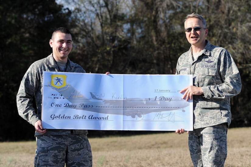 """Col. Darren Hartford, 437th Airlift Wing commander, presents the """"Golden Bolt Award"""" to Airman 1st Class Donald Kinlin  after the Foreign Object Debris walk Jan. 17, 2013, at Joint Base Charleston - Air Base, S.C. JB Charleston  brought he fun of treasure hunting into its FOD walk, by hiding a prized """"Golden Bolt"""" along the flight line. By removing FOD from runways and flightlines, Airmen help save the Air Force millions of dollars in costly engine repairs and replacement every year. (Courtesy photo)"""