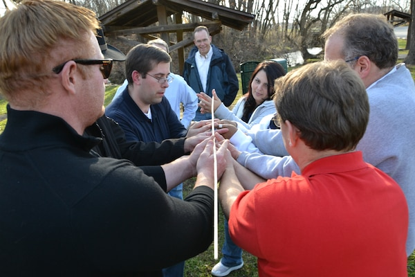 "A Tier II team attempts to bring a ""helium stick"" to the ground through use of leaderships skills and teamwork. (Photo by Kristin Hoelen)"