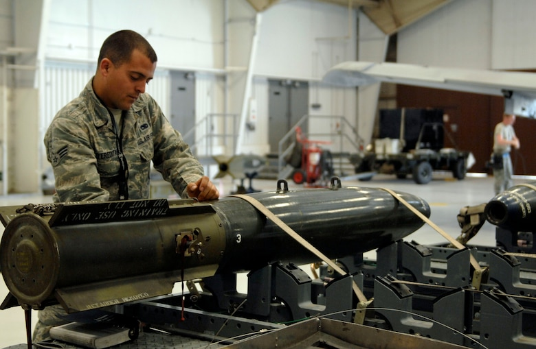 U.S. Air Force Senior Airman Adam D'Eredita, 355th Aircraft Maintenance Squadron, participates in a practice weapons load in a hanger at the 355th Maintenance Operations Squadron on Davis-Monthan Air Force Base, Ariz., Jan. 23, 2012. Instructors from the 355th MOS observed as the three-man team successfully loaded 500-pound bombs onto an aircraft. (U.S. Air Force photo by Senior Airman Saphfire Cook)