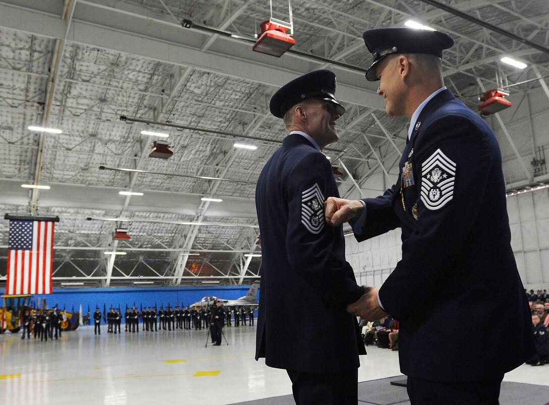 The newly retired Chief Master Sgt. of the Air Force James Roy tacks on the chevron of Chief Master Sgt. of the Air Force James Cody at a transition and retirement ceremony, Jan. 24, 2013, on Joint Base Andrews, Md. Roy, the 16th chief master sergeant of the Air Force, retired after more than 30 years of service to the Air Force. (U.S. Air Force photo/Jim Varhegyi)
