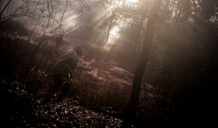 Airmen from the 1st Combat Camera Squadron pose as opposing forces as they prepare to ambush a convoy during the Ability to Survive and Operate exercise Jan. 18, 2013, at North Auxiliary Air Field, S.C. Combat Camera held the exercise to train Airmen to function outside the wire as combat documentation specialists. The week-long exercise began Jan. 7 and ended Jan. 18. The 1st CTCS acquires still and motion imagery in support of classified and unclassified air, sea and ground military operations. (U.S. Air Force photo/Senior Airman Dennis Sloan)