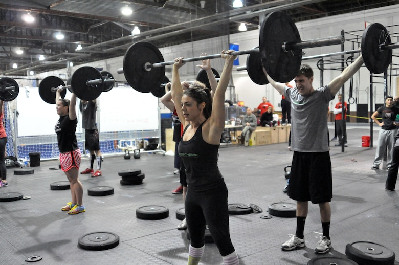 CrossFit Omaha's Andrea McDaniel and her teammate Matt Behrens hold a press while their teammates complete 10 tire flips. (U.S. Air Force Photo by 2nd Lt. Carly Costello/Released)