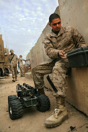 Cpl. Raul Cardenas, 24, from Santa Ana, Calif., vehicle commander for 2nd Squad, Security Company, Combat Logistics Battalion 5, 1st Marine Logistics Group, prepares a Multi-function Agile Remote Control Robot prior to a mission Dec. 20. Security Co. uses the MARCbot to safely investigate possible Improvised Explosive Devices. Security Co. ensures that convoys reach their destination safely by providing security throughout the trip.