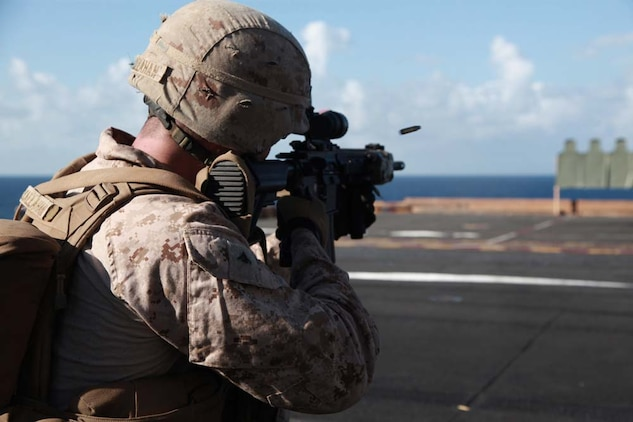 Lance Cpl. Ryan S. Callahan, automatic gunner, 3rd Platoon, Kilo Company, Battalion Landing Team 3/5, 15th Marine Expeditionary Unit, fires his Infantry Automatic Rifle at targets on the flight deck of the USS Peleliu, Jan. 22. Kilo Company is one of three rifle companies in BLT 3/5, the 15th MEU's ground combat element. The 15th MEU is deployed as part of the Peleliu Amphibious Ready Group as a U.S. Central Command theater reserve force, providing support for maritime security operations and theater security cooperation efforts in the U.S. 5th Fleet area of responsibility. Callahan, 24, is from Bluffton, S.C. (U.S. Marine Corps photo by Cpl. John Robbart III)