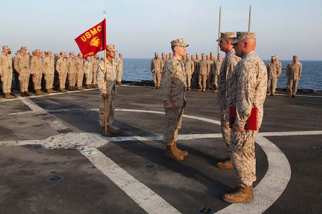 First Sgt. Bradley G. Simmons (center), Sergeant Major,  Combat Logistics Battalion 15, 15th Marine Expeditionary Unit, stands in front of Lt. Col. John Wiener, commanding officer, CLB-15, 15th MEU, before being presented the Bronze Star with Combat Distinguishing Device, aboard the USS Rushmore, Jan. 25. Simmons, 34, is a native of Liberal, KS. The 15th MEU is deployed as part of the Peleliu Amphibious Ready Group as a U.S. Central Command theater reserve force, providing support for maritime security operations and theater security cooperation efforts in the U.S. 5th Fleet area of responsibility. (U.S. Marine Corps photo by Cpl. Timothy R. Childers)