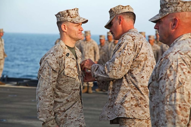 Lieutenant Col. John Wiener, commanding officer, Combat Logistics Battalion 15, 15th Marine Expeditionary Unit, pins the Bronze Star with Combat Distinguishing Device on 1st Sgt. Bradley G. Simmons, Sergeant Major, CLB-15, 15th MEU, during his award ceremony aboard the USS Rushmore, Jan. 25. Simmons, 34, is a native of Liberal, KS. The 15th MEU is deployed as part of the Peleliu Amphibious Ready Group as a U.S. Central Command theater reserve force, providing support for maritime security operations and theater security cooperation efforts in the U.S. 5th Fleet area of responsibility. (U.S. Marine Corps photo by Cpl. Timothy R. Childers)