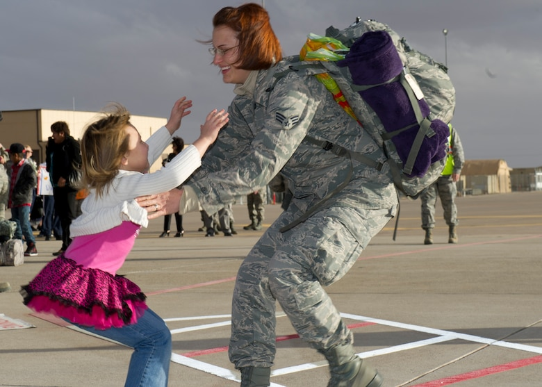 A Senior Airman returning from deployment greets her daughter after landing on the Holloman AFB, N.M., flightline Jan. 28.  F-22 Raptors and around 200 personnel returned Monday from a 9-month deployment to Southwest Asia ensuring regional security and joint tactical air operations. (U.S. Air Force photo by Airman 1st Class Michael Shoemaker/Released)