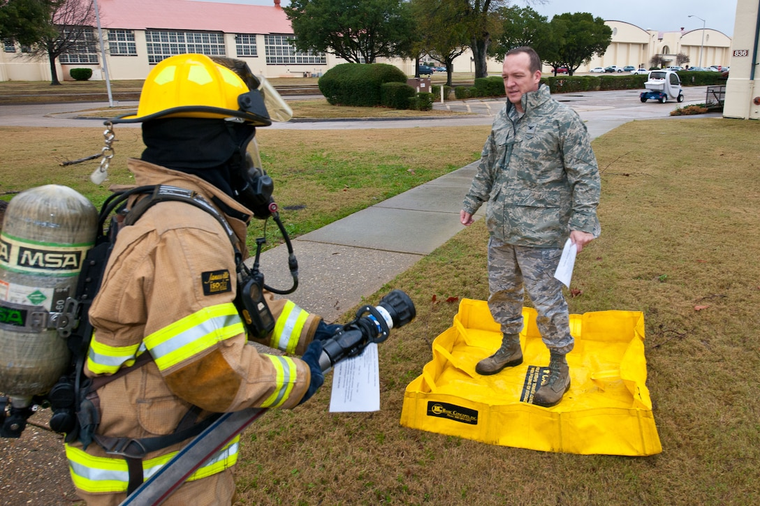 A member of the hazardous materials team simulates hosing down Col. Matthew Brand, Spaatz Academic Center's director, as part of the decontamination process on Maxwell Air Force Base during a nerve-agent exercise Jan 17. (U.S. Air Force photograph by Donna L. Burnett)