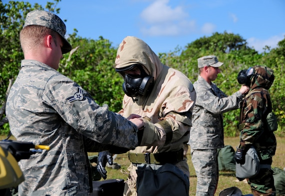Instructors from the 36th Civil Engineer Squadron readiness and emergency management flight demonstrate how to properly wear their chemical gear during chemical warfare, post-attack reconnaissance training at Andersen Air Force Base, Guam, Jan. 28, 2013. The 36th CES readiness and emergency management flight's primary mission is to manage programs that save lives, minimize the loss or degradation of resources and to sustain and restore operational capability through hazardous physical and environmental threats. (U.S. Air Force photo/Airman 1st Class Marianique Santos/Released)