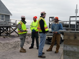 New York Recovery Field Office Commander Lt. Col. John A. Knight (at left) and RFO Operations Chief Sean O'Donnell speak with local homeowners, Fire Island, N.Y., Jan. 11, 2013. The Corps of Engineers and the municipalities on Fire Island are exploring alternate ways of removing debris from the narrow walkways and paths that exist on the remote barrier.